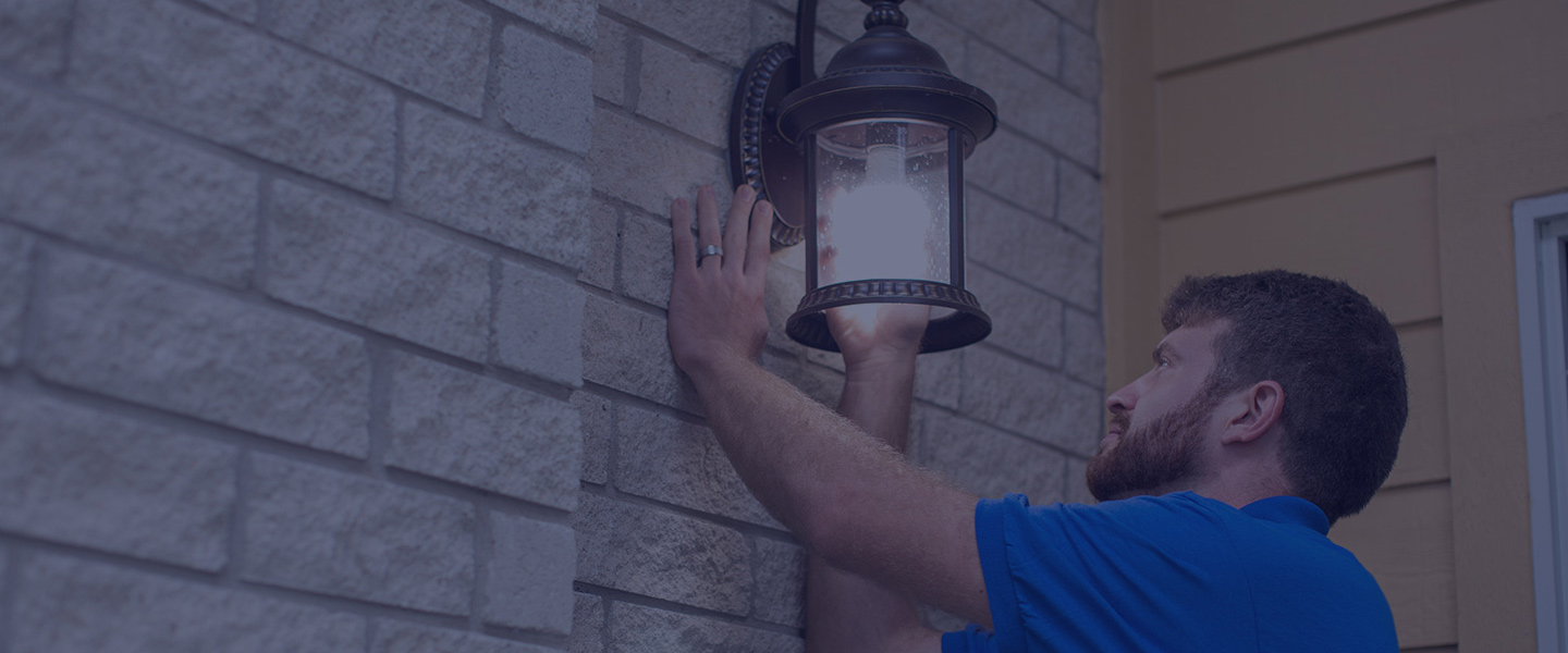 man changing lightbulb on home exterior